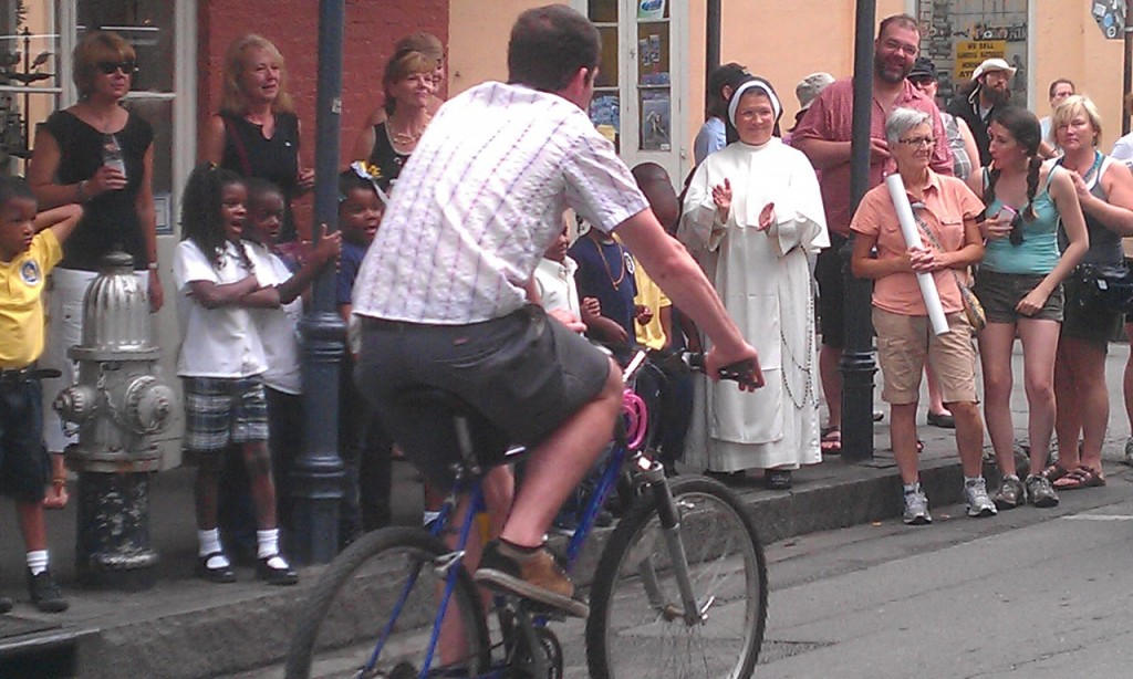 Guy on bike passes nun on street